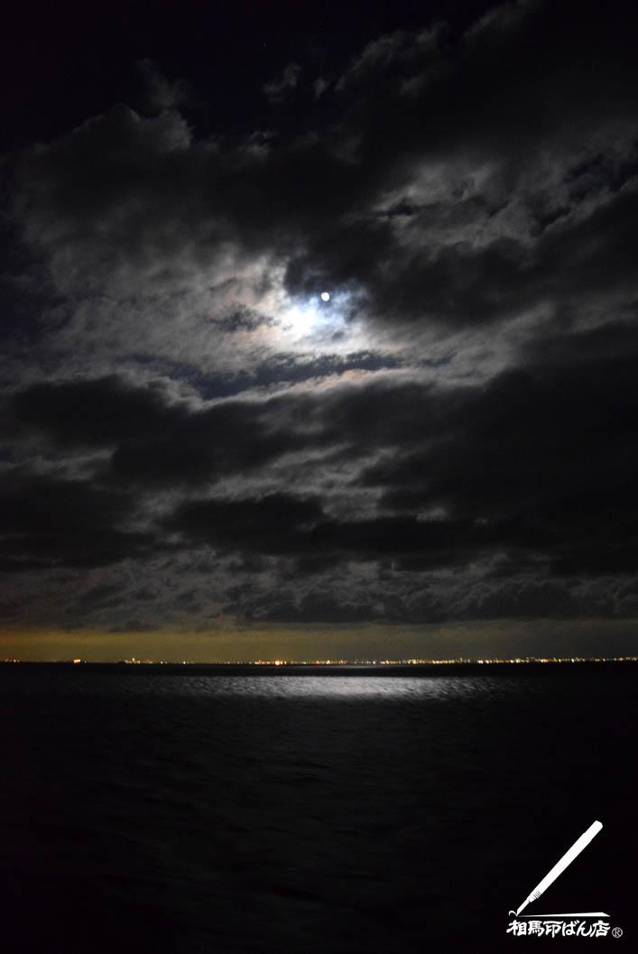 満月の光が雲に遮られて海上をスポットで照らす。