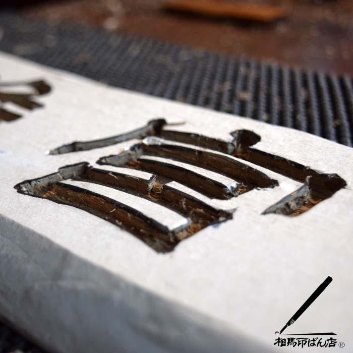ノミで刻す木製の看板