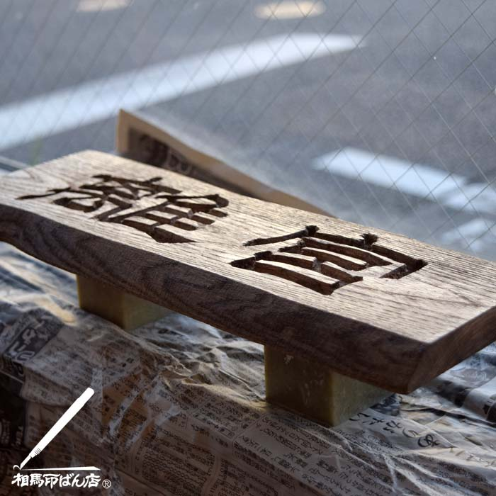 刻字でつくった木製の看板にニスを塗る