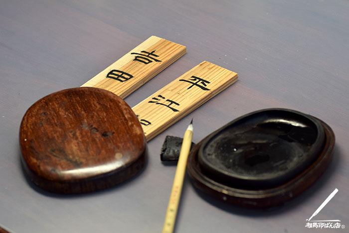 木札に隷書で名前を書き入れる